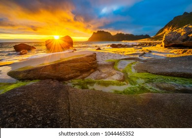 Dramatic sunset over Uttakleiv beach on Lofoten islands in Norway with a natural pond in the foreground. Hdr processed.