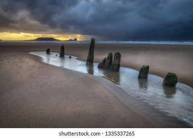 Dramatic sunset over the wreck of the Helvetia at Worms Head and Rhossili Bay on the Gower peninsula, Swansea, South Wales, UK