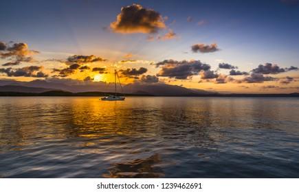 dramatic sunset Port Douglas reflections Coral sea Daintree sunburst tropical Queensland mountain range rainforest yacht