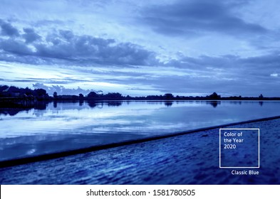 Dramatic sunset scene with cloudscape over the the horizon and lake in Ukraine toned in blue. Main color trend of the year 2020.
