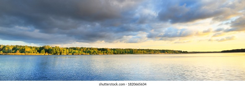 Dramatic sunset sky with glowing golden cirrus and cumulus clouds above the river and forest before the rain. Idyllic rural scene. Panoramic view. Vacations, eco tourism, nature of Scandinavia