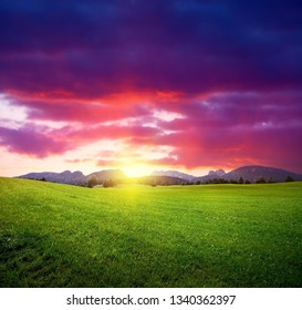 Dramatic sunset sky and green meadow with mountains on horizon. Summer landscape