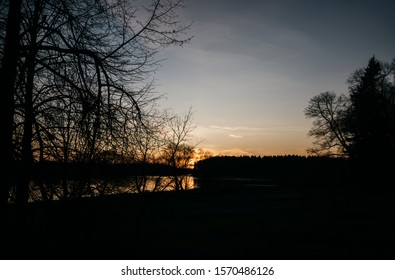 Dramatic sunset sky over river and forest with silhouette trees