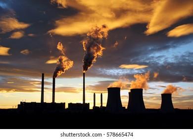 dramatic sunset and smoking power plant