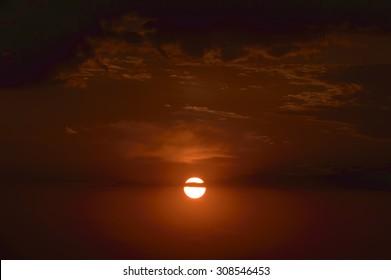 Dramatic sunset sun in clouds.