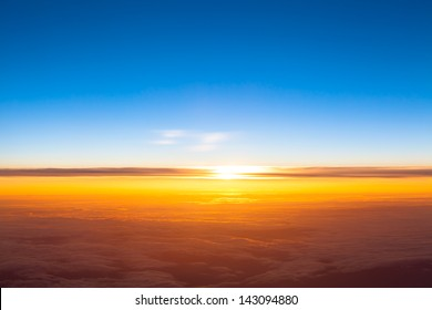 Dramatic sunset. View of sunset above clouds from airplane window