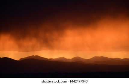 dramatic sunset and virga clouds over the front range of the colorado rocky mountains, as seen from broomfield, colorado