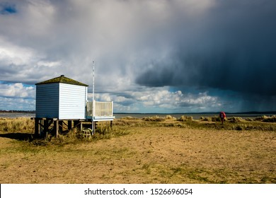 Dramatic sweeping storm clouds contrast with sun shining on beach huts at Hengistbury head, Dorset England