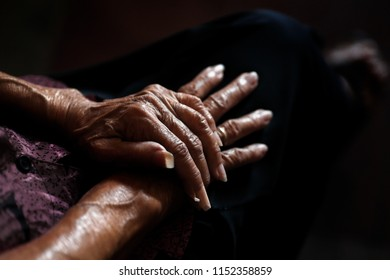 A dramatic take on a pair of old woman hands together in a very low key enviroment, higlighting the details of age wrinkles.