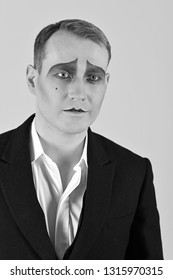 Dramatic and tragic. Unhappy mime with face paint. Theatre actor miming. Mime artist. Man with mime makeup. Stage actor playing. Theatrical performance art and pantomime. Drama or tragedian performer.
