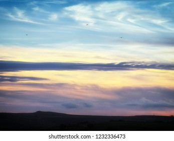 dramatic twilight cloudscape with dark horizon and three small birds flying above the clouds
