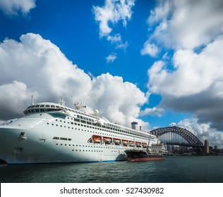 Dramatic view of cruise ship with massive white cloud and blue sky in Sydney harbour, Australia.