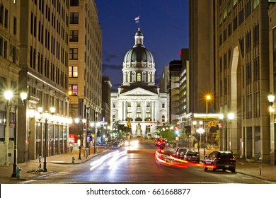 A dramatic view of the Indiana capitol building at night in Indianapolis, with busy streets and a long exposure