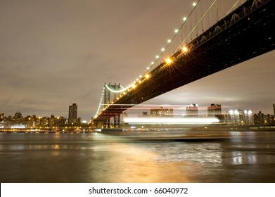 A dramatic view of the New York City skyline at night including the Manhattan Bridge