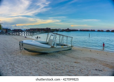 dramatic view old speed boat in beach and human  in mabul island with refraction of sunset