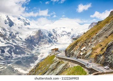 Dramatic view on the Grossglockner, seen from the Kaiser-Franz-Josefs-Höhe in the national wildpark in Tyrol, Austria. Partially snow covered mountains, shot against a partially clouded sky.