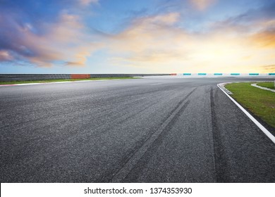 Dramatic view of racing asphalt road with evening sky.