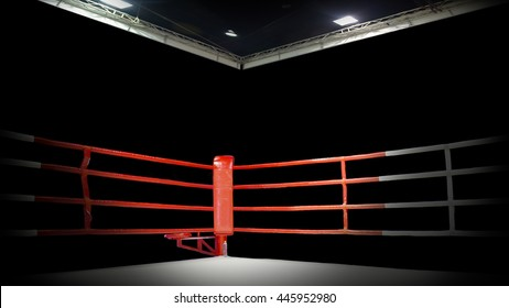 A dramatic view of the red corner of a regular boxing ring surrounded by ropes spotlit by a spotlight on an isolated dark background