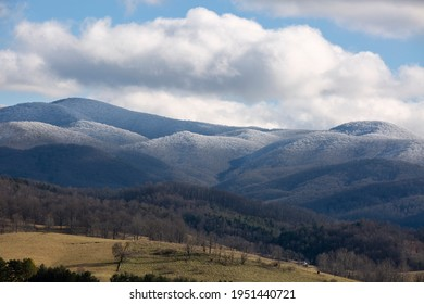 Dramatic view of snow covered Appalachian mountains under blue sky in Virginia.