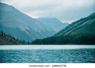 Dramatic view to vast mountain lake among giant mountains in rainy weather. Pines and larches on hillside near azure water. Overcast landscape with turquoise alpine lake. Atmospheric highland scenery.