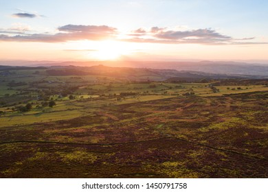 Dramatic warm sunset light over upland hills and farming fields at summer evening. Shropshire Hills in United Kingdom
