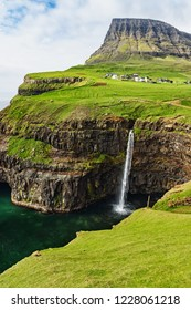 Dramatic waterfall on Faroe Islands and the village Gasadalur