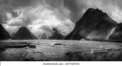 Dramatic weather conditions at Milford Sound in black and white, view at Freshwater Basin towards the fjord's entry, with Bowen and Stirling falls in Fordland National Park, New Zealand, South Island.