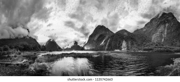Dramatic weather conditions at Milford Sound in black and white with the clouds engulfing the mountain peaks -Panoramic view with Bowen Falls and Mitre Peak in Fordland National Park, New Zealand.