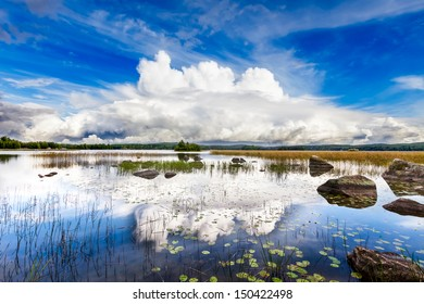 Dramatic white cloud over a bright blue lake on a sunny day