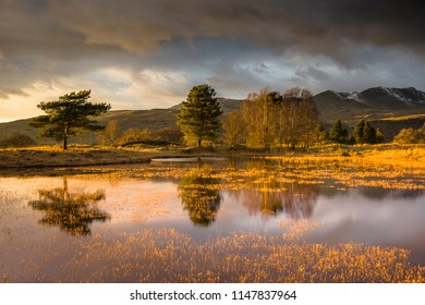 Dramatic winter light over Kelly Hall Tarn, Torver at sunset. Not far from the town of Coniston, Lake District.