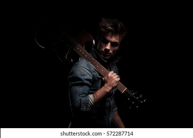 dramatic young guitarist looking back while holding guitar on shoulder, on black studio background