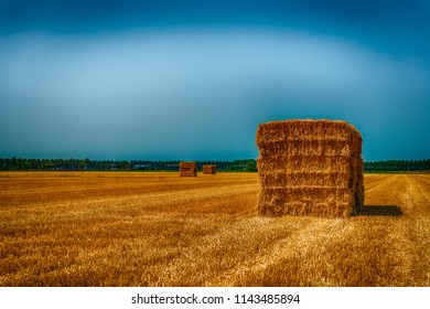 Dramatically colored image of rectangular bales of straw stacked on a stubble field after harvesting the wheat. The exaggerated colors have an almost mystical effect on the image.