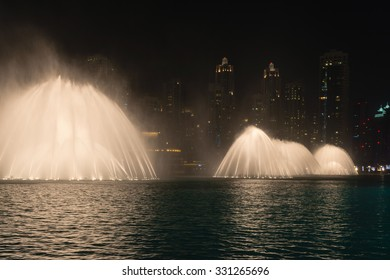 Dramatically lit fountains throwing white curtains of water into the air along the tropical beachfront of a major metropolitan city at night.