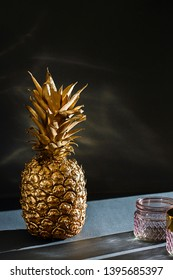 Dramatically lit golden colored pineapple in a studio setup.