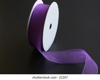 A dramaticly sidelit spool of purple ribbon, unwinding on a black background, with room for advertising copy. Thumbnail doesn't show woven thread detail in ribbon; actual photo does. Concepts: unwound, unwind.