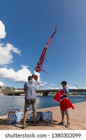 Drammen, Norway - 25. August, 2018: Father and son with a long tail kite of Norwegian flags. Large flag is about to be attached to the end. Drammen Elvefestival