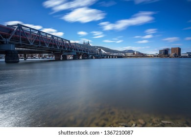 Drammen/ Norway - April 9 2019: Railroad bridge in Drammen with a local train passing