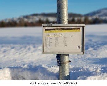 Drammen, Norway - February 22, 2018: Schedule at the bus stop with snowy background in a sunny day