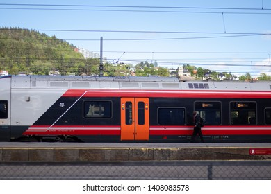 Drammen, Norway - May 26th 2019: Red train in train-station. Passenger about to board.