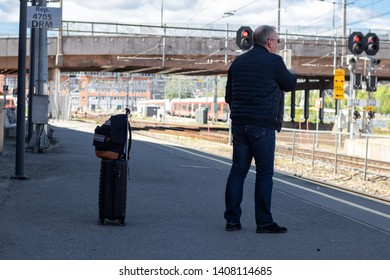 Drammen, Norway - May 26th 2019: Older man with luggage waiting for the train, on the train-station platform.