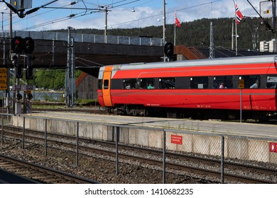 Drammen, Norway - May 26th 2019: Red train leaving train-station.