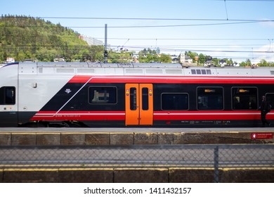 Drammen, Norway - May 26th 2019: Red, black and orange train parked in train-station.