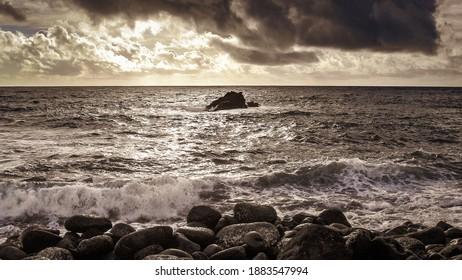 dramtic ocean view from a rocky coastline with stormy sky