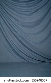 Draped canvas or muslin fabric cloth studio backdrop or background, suitable for use with portraits, products and concepts. Muted blue color.
