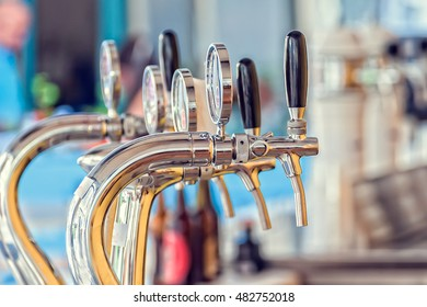 Draught beer taps and other beverages in a bar.