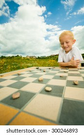 Draughts board game. Little boy clever child kid playing checkers thinking, outdoor in the park. Childhood and development