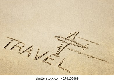 Drawing of an airplane and a word travel on sandy surface.