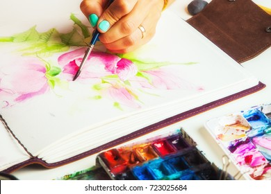Drawing album with painted peonies and dogroses on a white table, top view