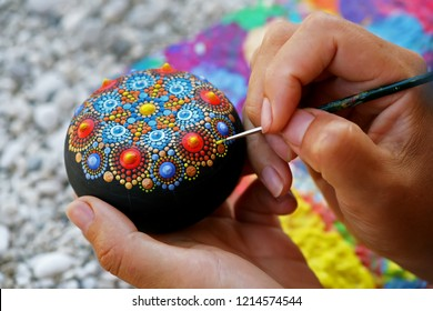 Drawing with a brush a dot mandala on a stone