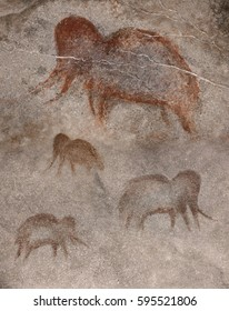 Drawing in a cave by an ancient Neanderthal man. Paint ocher. Group of mammoths. Cave man, wall, rock, primitive, prehistoric.